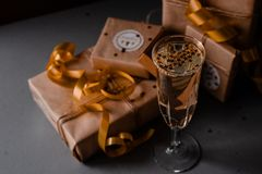 Champagne Glass Presents Decorations Background. Golden bonnets, standing on a dark table royalty free stock photo