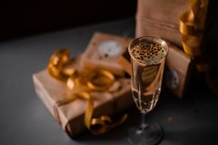 Champagne Glass Presents Decorations Background. Golden bonnets, standing on a dark table stock photo