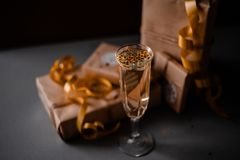 Champagne Glass Presents Decorations Background. Golden bonnets, standing on a dark table royalty free stock image