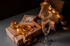 Champagne Glass Presents Decorations Background. Golden bonnets, standing on a dark table royalty free stock photos