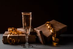 Champagne Glass Presents Decorations Background. Golden bonnets, standing on a dark table stock photos