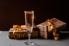 Champagne Glass Presents Decorations Background. Golden bonnets, standing on a dark table royalty free stock photography