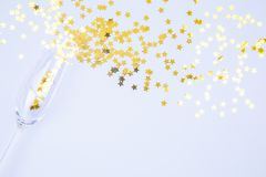Champagne glass with sprinkles on blue background. Holiday, part royalty free stock photos
