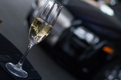Champagne glass on table with high end car in background. Champagne glass filled with champagne against dark background with luxury automobile royalty free stock photos