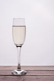 Champagne glass on wooden table against white background Royalty Free Stock Photo
