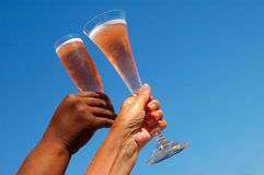 Champagne glasses. An African American black female hand and a caucasian white female hand holding a champagne glass with red sparkling wine in front of blue sky Royalty Free Stock Photo
