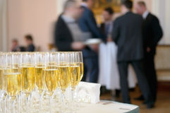Champagne glasses. Champagne glasses against the background of business people Stock Image