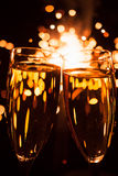 Champagne glasses against sparkler background Stock Photos