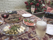 Champagne glasses and appetisers on table. At garden Royalty Free Stock Photo