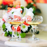 Champagne in glasses on  background of a bouquet of flowers at Royalty Free Stock Photography