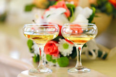 Champagne in glasses on  background of a bouquet of flowers at Stock Photos