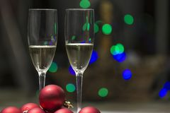 Champagne glasses with balls and christmas lights stock photography