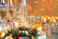 Champagne in glasses,candles,baubles and lights. Stock Photos