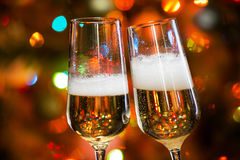 Champagne glasses and Christmas lights Stock Photos