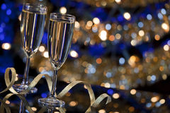 Champagne glasses with Christmas lights in the background Royalty Free Stock Images