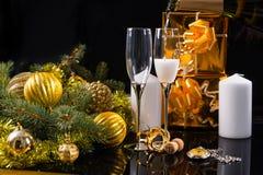 Champagne Glasses con las velas y los regalos de la Navidad Foto de archivo libre de regalías