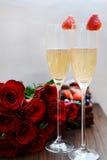 Champagne Glasses con le fragole ed il mazzo di fiori Fotografia Stock Libera da Diritti