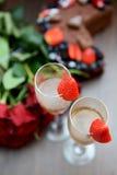Champagne Glasses con le fragole ed il mazzo di fiori Immagine Stock Libera da Diritti