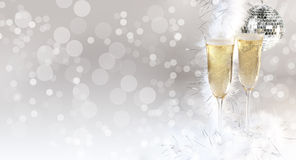 Champagne Glasses Filled. Two full champagne flutes with mirrored disco party ball in bokeh background and copy space to left of image. Concept for party, new Stock Photos
