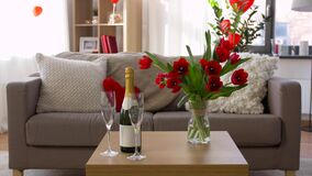 Champagne, glasses and flowers at valentines day. Valentines day, holidays and interior concept - bottle of champagne, two glasses and red tulip flowers on table stock footage