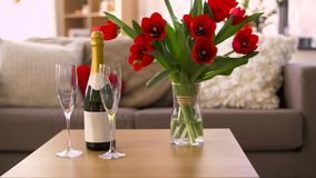 Champagne, glasses and flowers at valentines day. Valentines day, romantic date and holidays concept - bottle of champagne, two glasses and red tulip flowers on stock video footage