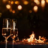 Champagne glasses in front of a log fire. And gold bokeh for a solemn occasion Royalty Free Stock Photos