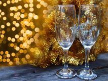 Champagne glasses on the frosted table. Champagne glasses on the frosted table, bokeh and garland tinsel in the background stock image