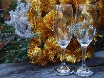 Champagne glasses on the frosted table. Champagne glasses on the frosted table, garland tinsel in the background royalty free stock photos