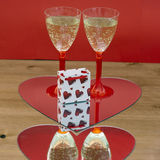 Champagne glasses and gift box in heart Stock Photos