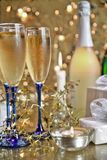 Champagne in glasses, gift box and lights Royalty Free Stock Photo