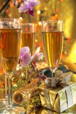 Champagne in glasses,gift and flowers. Champagne in glasses,gift box,bottle,flowers and lights on golden background Stock Images