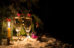Champagne glasses and glowing candles on snow Stock Images