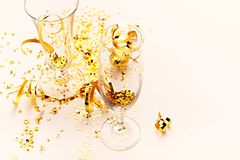 Champagne glasses with golden glitter on pink background. New Year concept stock image