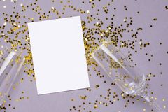 Champagne glasses with golden stars confetti and white card on gray color paper background minimal style stock image