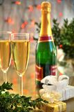 Champagne in glasses and green twig. Champagne in glasses, green twig and gifts on background with blured lights Stock Image