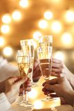 Champagne glasses in hands on golden background royalty free stock photo