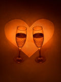 Champagne Glasses And Heart. Two glasses of champagne with a heart in the background.  Reddish-orange tint Stock Image