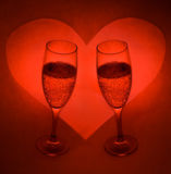 Champagne Glasses And Heart 2. Two glasses of champagne with a heart background.  Red tint to photo Royalty Free Stock Photography