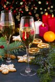 Champagne glasses in holiday setting. Christmas and New Year celebration with champagne. Christmas holiday decorated table with wh Stock Photos