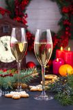 Champagne glasses in holiday setting. Christmas and New Year celebration with champagne. Christmas holiday decorated table with wh Royalty Free Stock Image