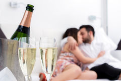Champagne glasses with kissing couple in background. Close up Champagne glasses and cold bottle in ice bucket with kissing couple in background Royalty Free Stock Photo