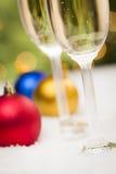 Champagne Glasses och julprydnader på snö Arkivbilder