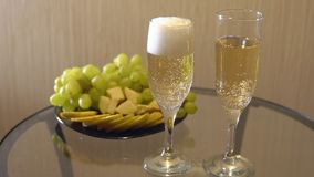 Champagne in glasses and a plate of fruit on the table. Slow motion stock video footage
