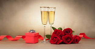 Champagne glasses, present and roses Royalty Free Stock Photos