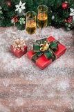 Champagne glasses set next to a pretty red gift box on table wit stock image