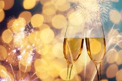 Champagne glasses on sparkling background. Glasses with champagne against fireworks and holiday lights - Celebrating the New Year Stock Images