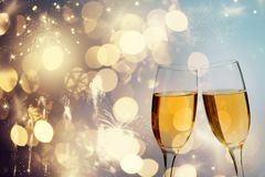 Champagne glasses on sparkling background. Glasses with champagne against fireworks and holiday lights - Celebrating the New Year Royalty Free Stock Images