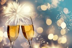 Champagne glasses on sparkling background. Glasses with champagne against fireworks and holiday lights - Celebrating the New Year Stock Photo
