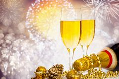 Champagne glasses on sparkling background. Glasses with champagne and Christmas decoration against fireworks and holiday lights - Celebrating the New Year Stock Photo