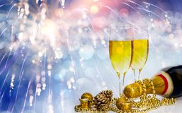 Champagne glasses on sparkling background. Glasses with champagne and Christmas decoration against fireworks and holiday lights - Celebrating the New Year Stock Images
